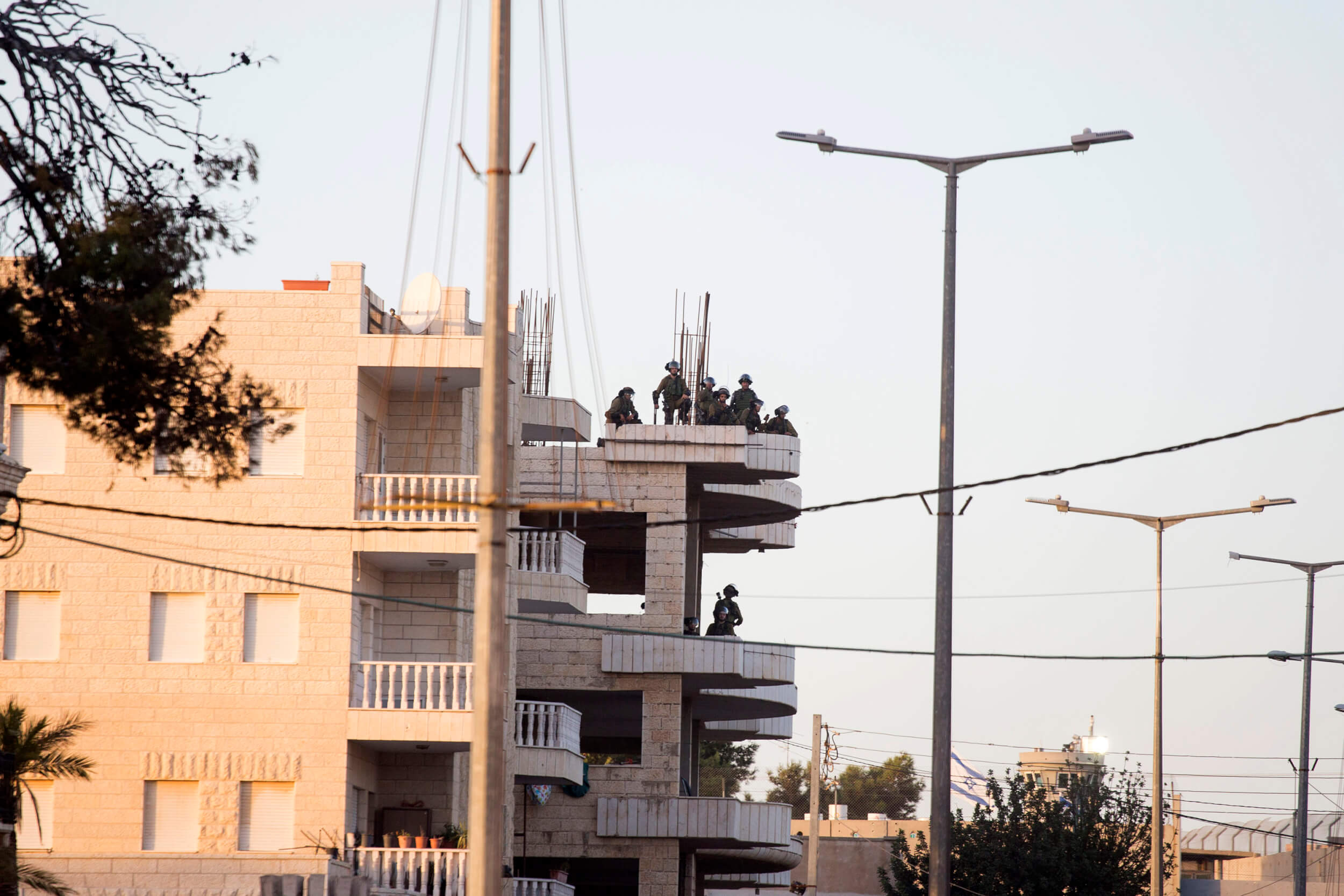 Israeli soldiers are seen on a top of a building inside Bethlehem. (Photo: Anne Paq)