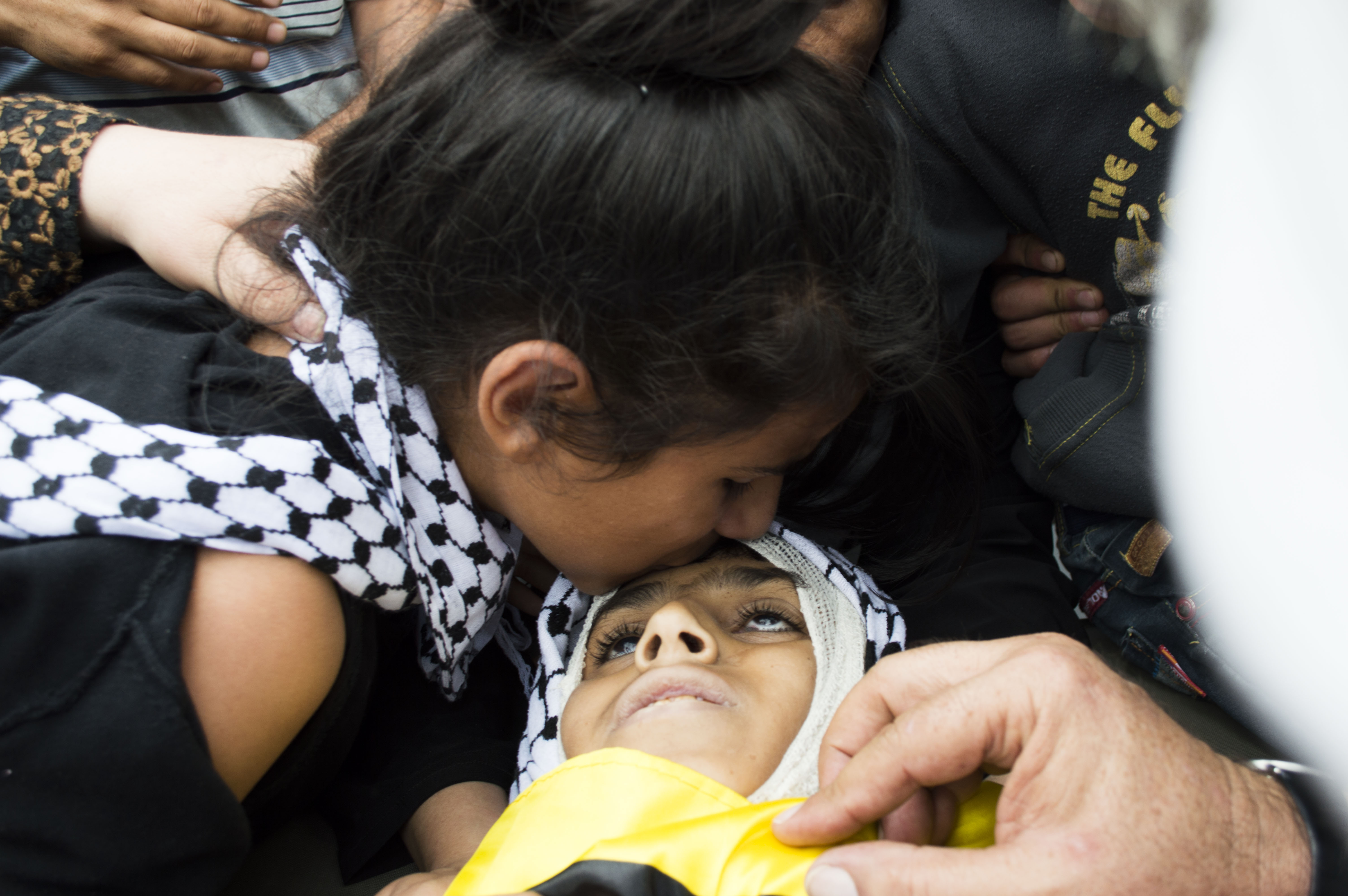 Abed Obeidallah's sister kisses the head of Abed before he is laid to rest.  (Photo by Abed al Qaisi)