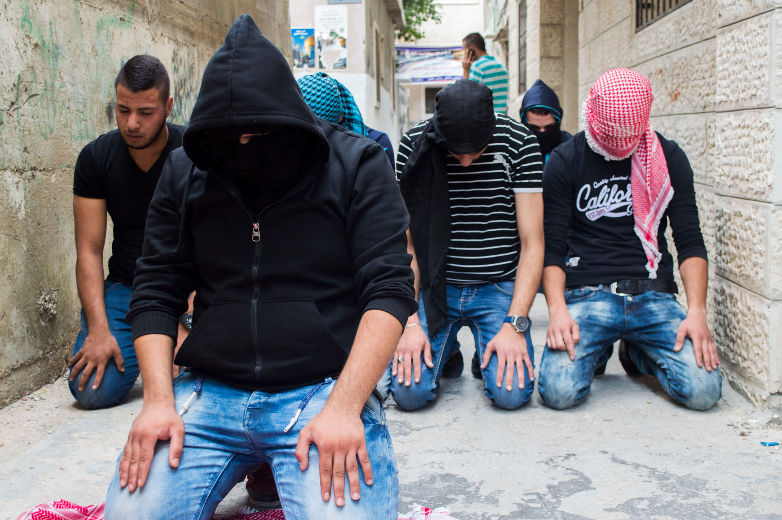 Young men pray for Abed outside the local mosque during midday prayers before he is laid to rest. (Photo by Abed al Qaisi)