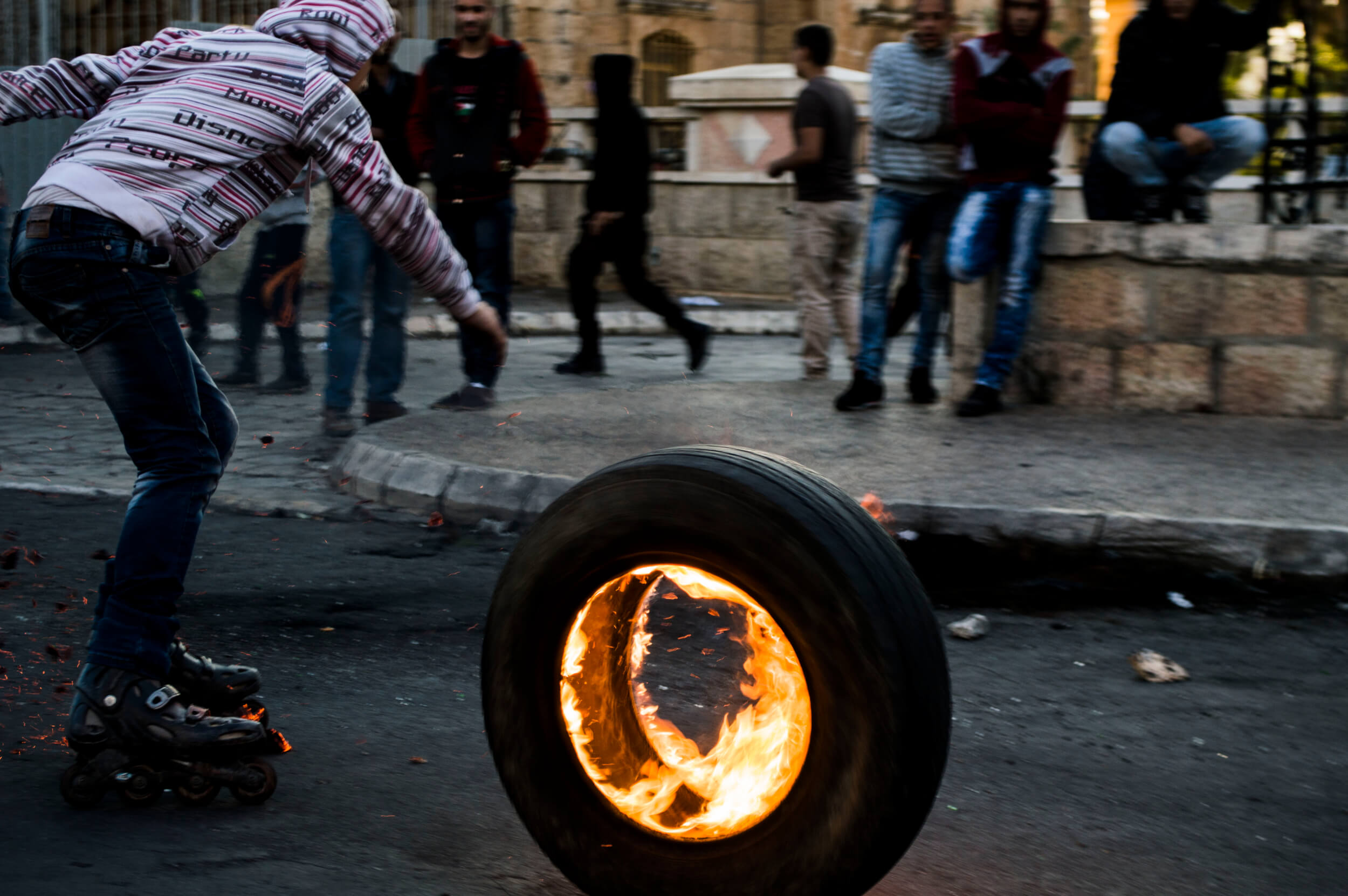 A boy on rollerblades rolls a flaming tire toward the frontline of clashes on Friday Oct. 9 in Bethlehem. (Photo: Sheren Khalel)