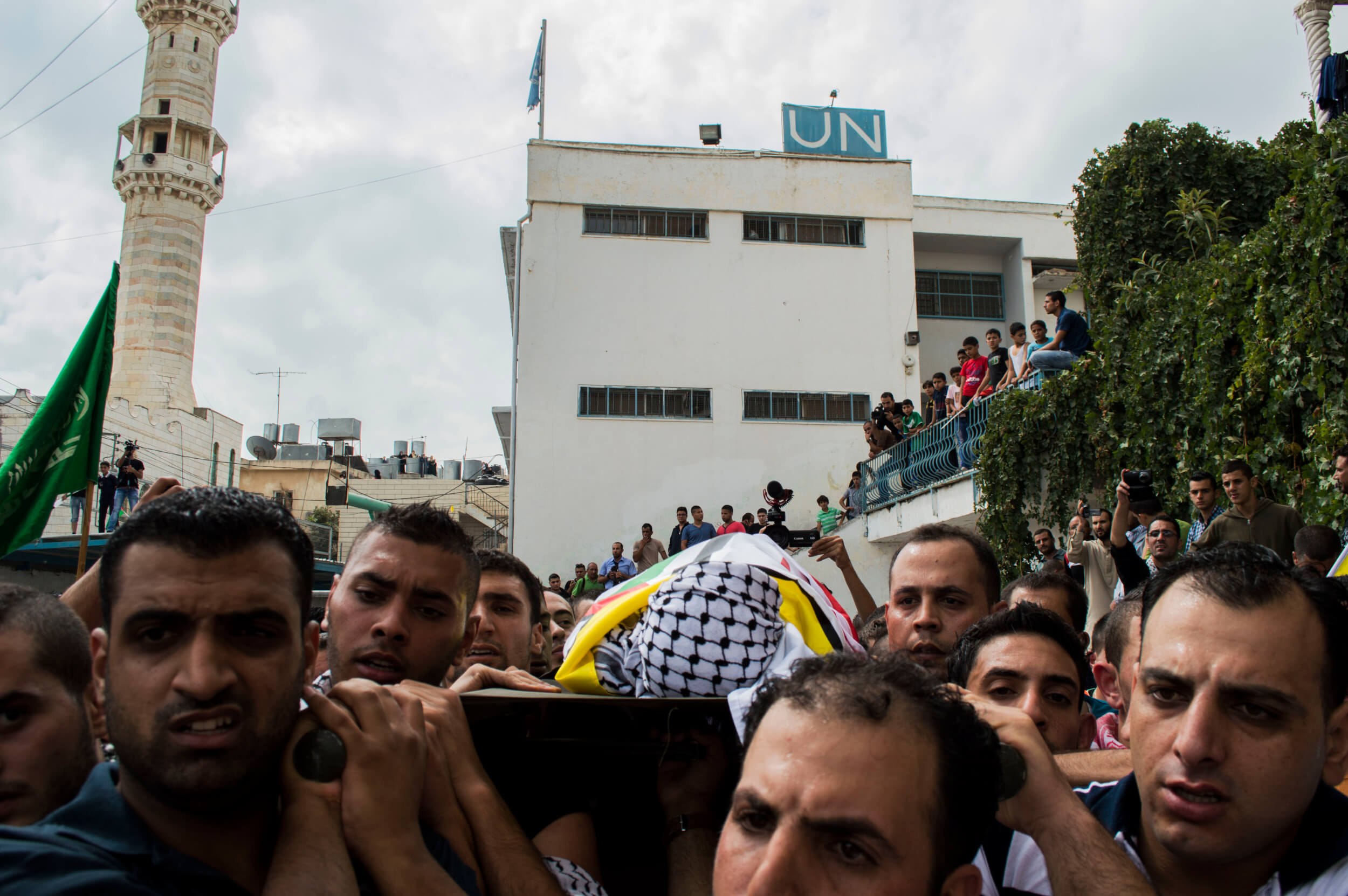 Family members carry Abed Obeidallah to the local cemetery, passing by the boy's UNRWA school. (Photo by Abed al Qaisi)