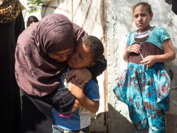 A Gaza woman comforts the surviving boy of the Hassan family, photo by Dan Cohen