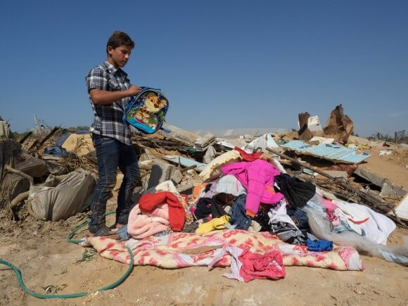 Abdullah Hassan combs through belongings where the house was bombed, in Gaza, photo by Dan Cohen