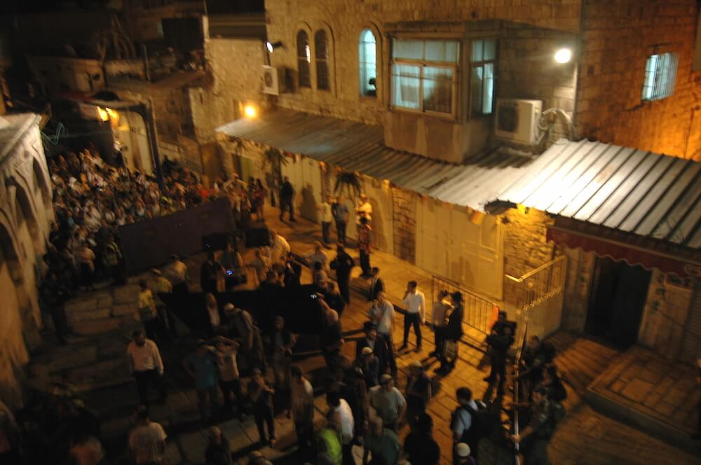 Israeli settlers march through the Muslim quarter in Jerusalem's Old City, Tuesday night. (Photo: Allison Deger)