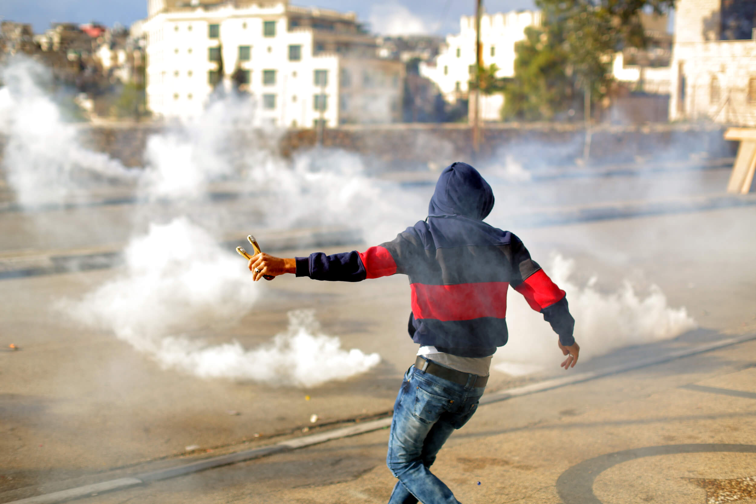 A Young man fires off one last rock from his sling shot before retreating away from the noxious gas. (Photo: Abed al Qaisi)