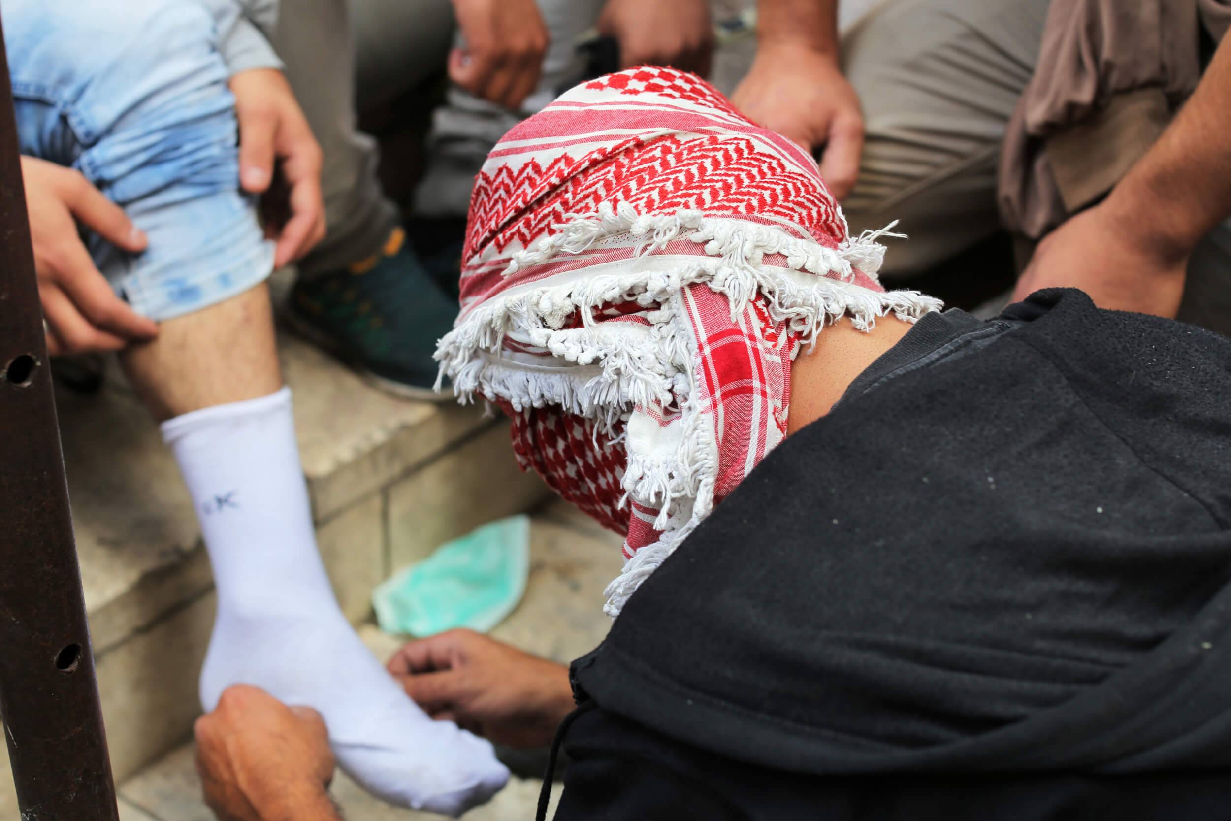 One protester examines the leg of another after he was hit with a tear gas canister during clashes. A hit with a canister can break the skin, cause bruising and chemical burns. (Photo: Abed al Qaisi)