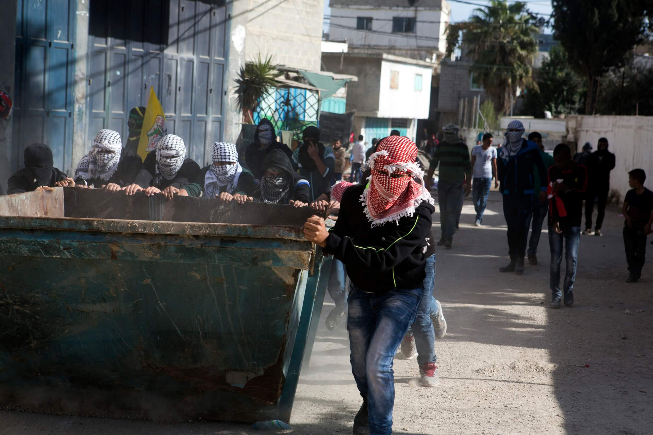 Garbage container becomes fortification after funeral in al-Arroub refugee camp, photo by Anne Paq