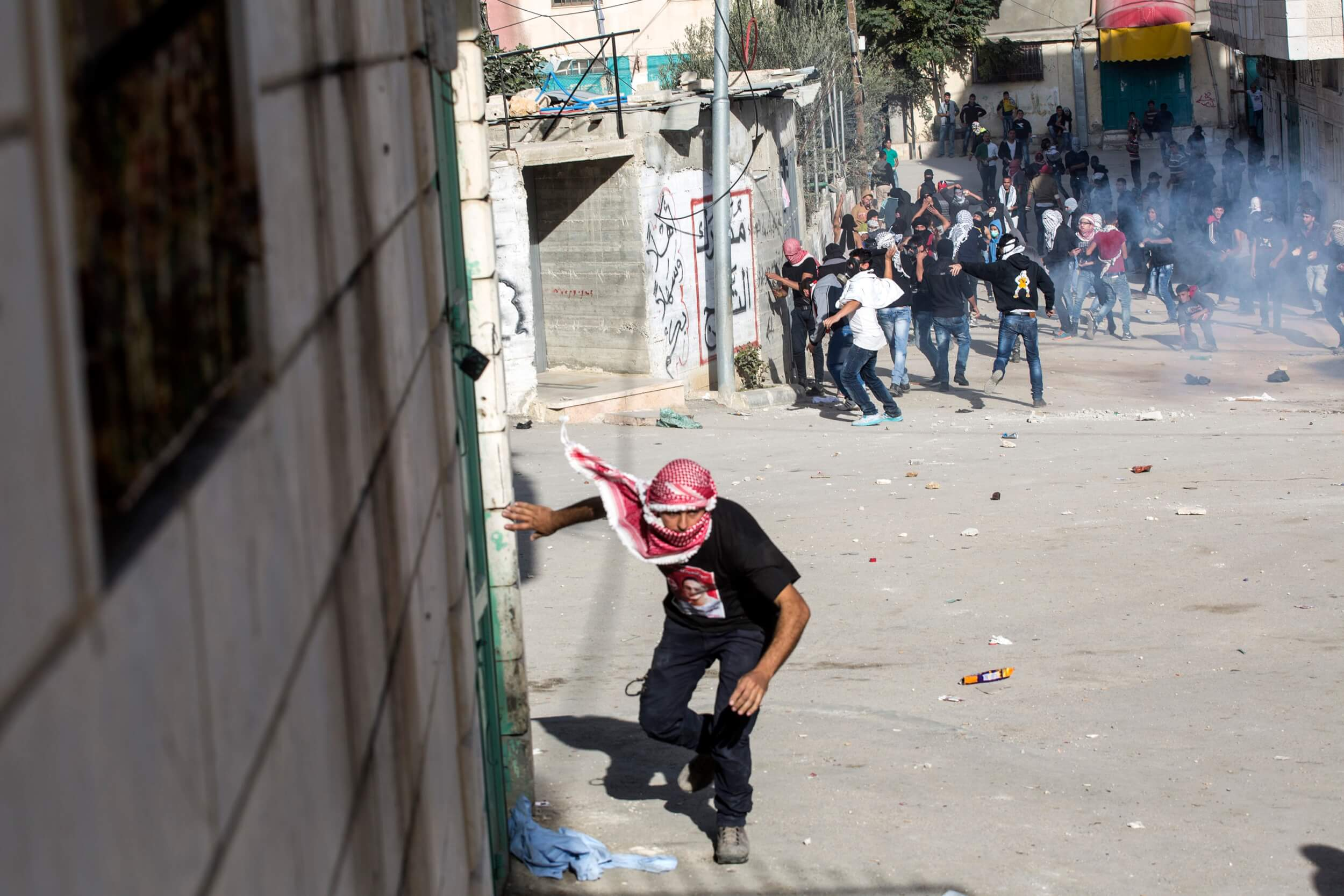 Palestinians take cover during clashes, al Arroub refugee camp