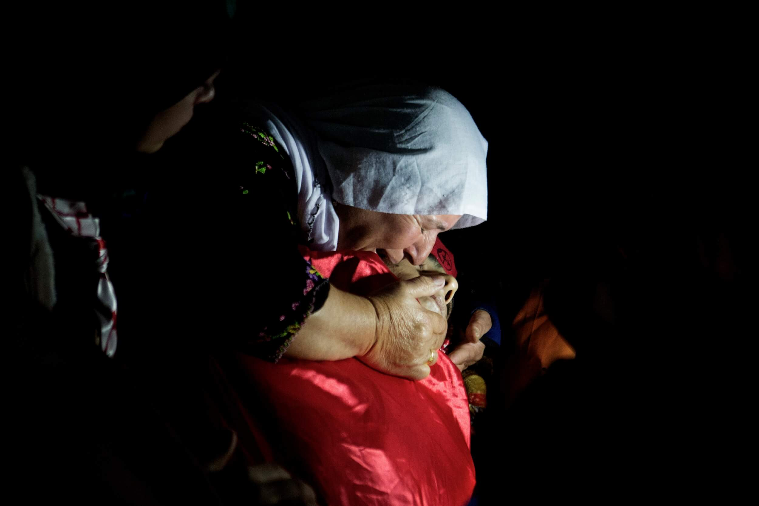A relative says goodbye to Khalid Mahmoud al-Jawabreh in Bethlehem, photo by Anne Paq