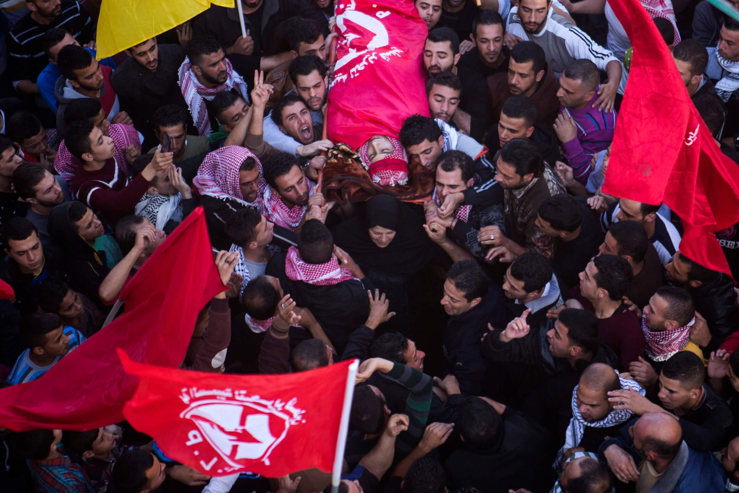 Khalid's mother helps to carry his body during Bethlehem funeral