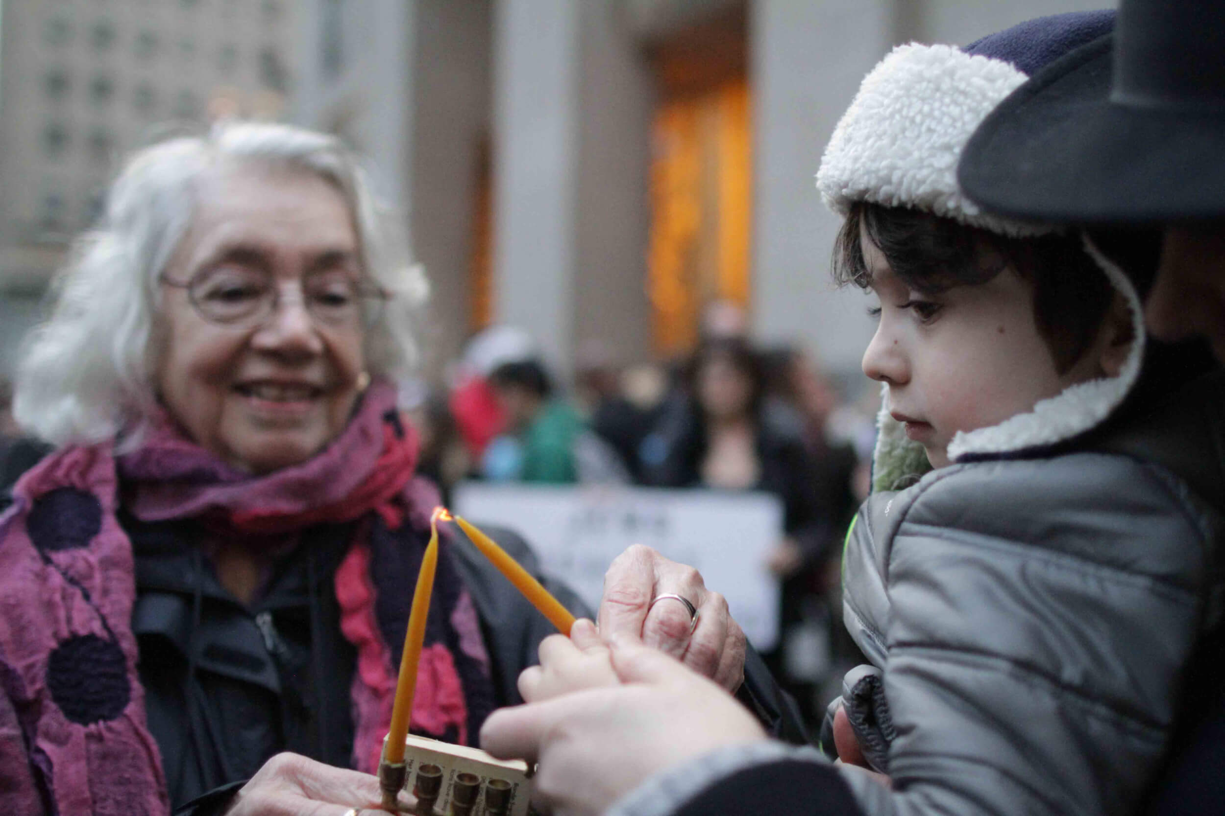 Dorothy Zellner and a young volunteer help light a menorah. (Photo: Jewish Voice for Peace)