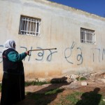 "A Palestinian woman stands next to a house sprayed with graffiti reading in Hebrew: ""revenge"" and ""hello from the prisoners of Zion"", in the village of Beitillu, near Ramallah in the Israeli occupied West Bank on December 22, 2015. Two tear gas canisters were also thrown into the Palestinian home by suspected Jewish extremists, Israeli police said, but the family there at the time was not hurt. (Photo: Shadi Hatem/APA Images)"