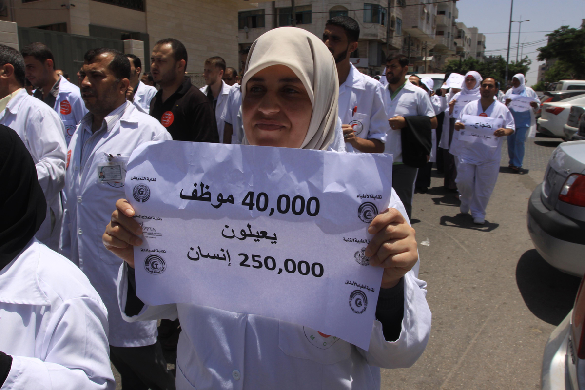 Palestinian health ministry employees  hold placards during a protest against not receiving their salaries, in Gaza City on June 30, 2014. (Photo: Mohammed Asad)