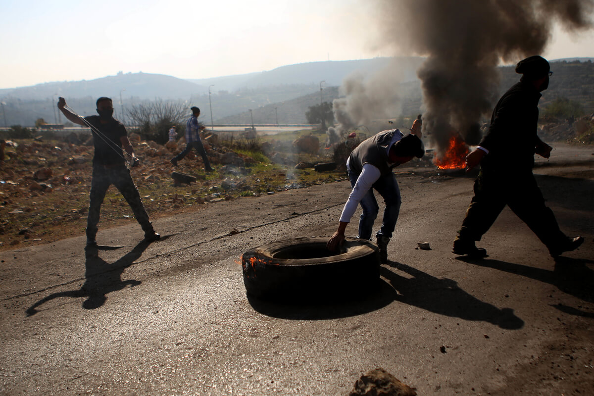 A Palestinian protester burns tires during clashes between Palestinian youth and Israeli army on in the occupied West Bank village of Silwad, northeast of Ramallah after a demonstration to call for the return of the bodies of killed alleged Palestinian attackers, December 11, 2015 (Photo: Shadi Hatem/APA Images/Mondoweiss)