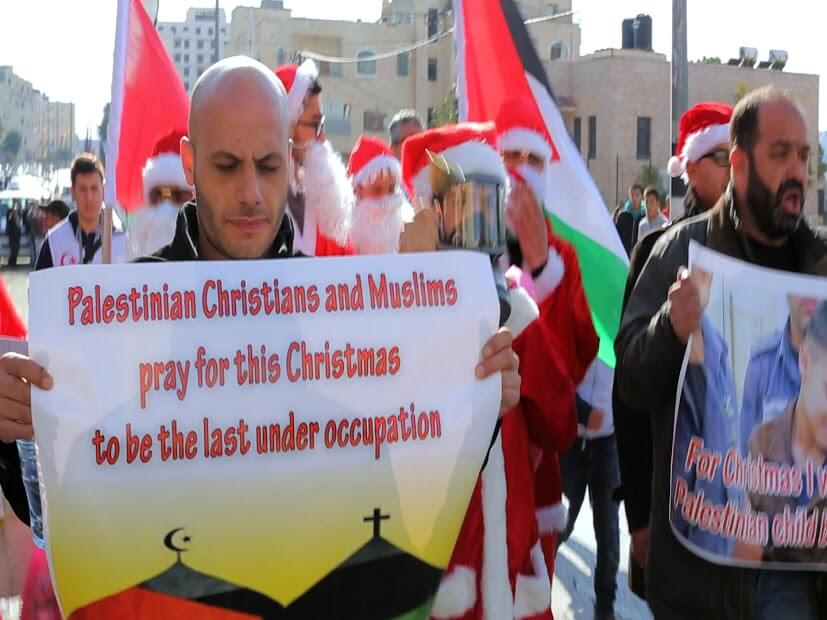 Protester holds sign Christians and Muslims pray for this Christmas to be he last under occupation