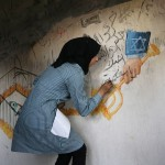 A Palestinian girl paints a graffiti on the wall in Dawabsha family's house in the village of Duma, near the occupied West Bank city of Nablus on September 7, 2015. (Photo: Shadi Hatem/APA Images)