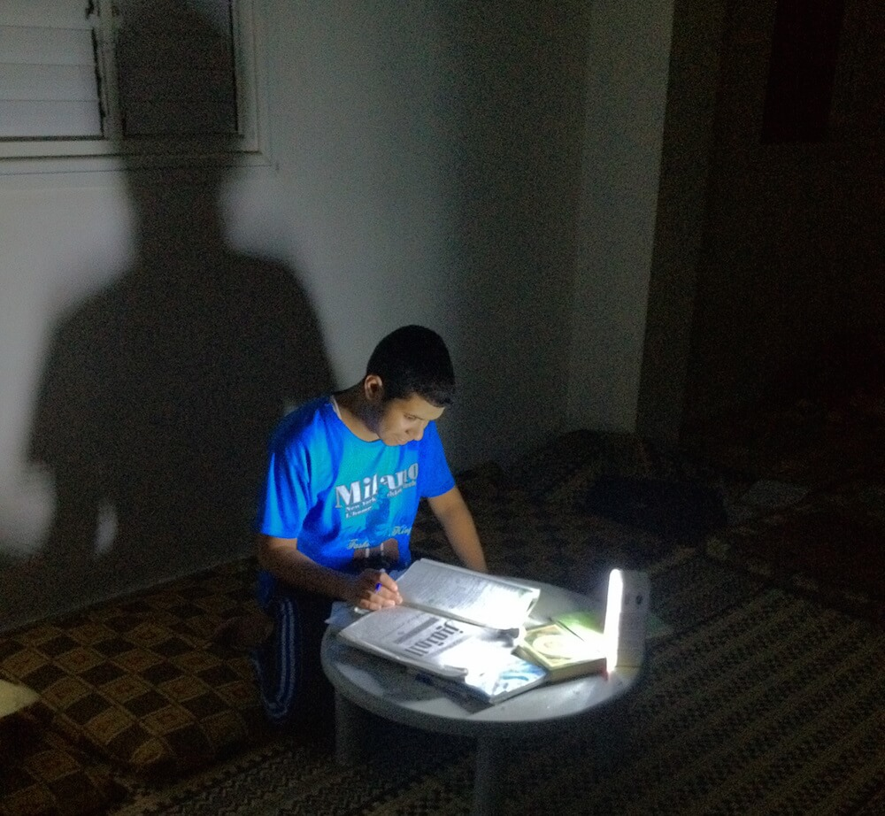 Ahmed Jaber's brother studies in the dark during Gaza's long hours of power outage. (Photo: Isra Saleh El-Namy)