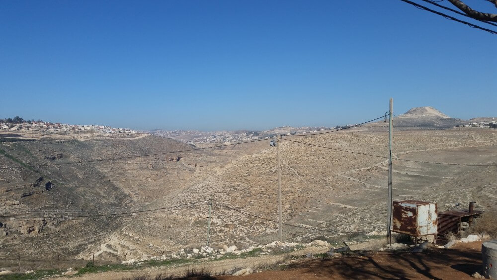 View north from Nokdim settlement in Gush Etzion bloc. Tekoa settlement is at left. In center foreground is security camera; in right background the Herodium