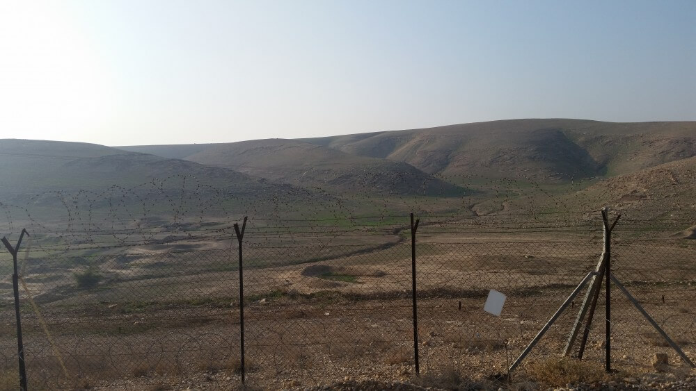 View to the west from kibbutz Na'aran in the Jordan Valley. Beyond security fence is the wadi and Judean hills.