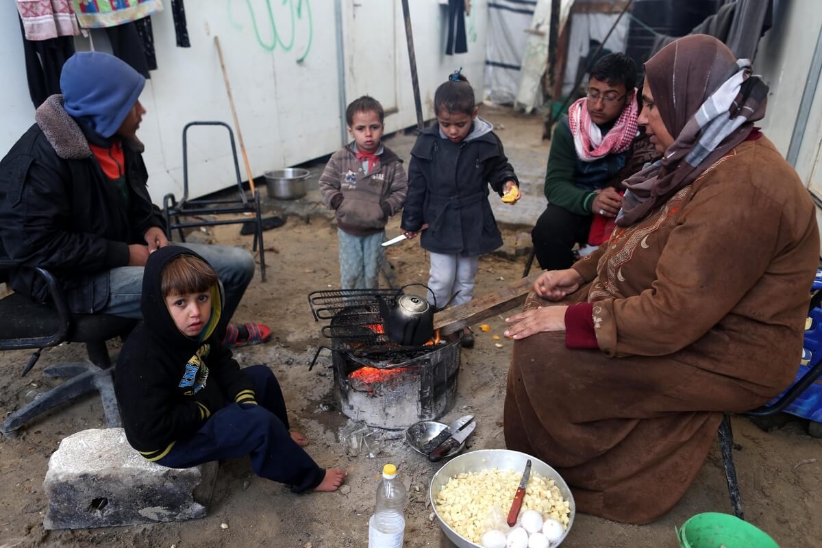 Members of a Palestinian family living in a container as a temporary replacement for their house that was destroyed by Israeli shelling during the 50 day war in 2014, warm themselves next to a fire during a rainy day in Beit Hanoun in the northern Gaza Strip, Jan. 24, 2016. (Photo: Mohammed Asad/ APA Images)