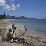 A homeless man drinks water while sitting on the beach at Ala Moana Beach Park located near Waikiki in Honolulu, Aug. 27, 2015. (AP Photo/Jae C. Hong)