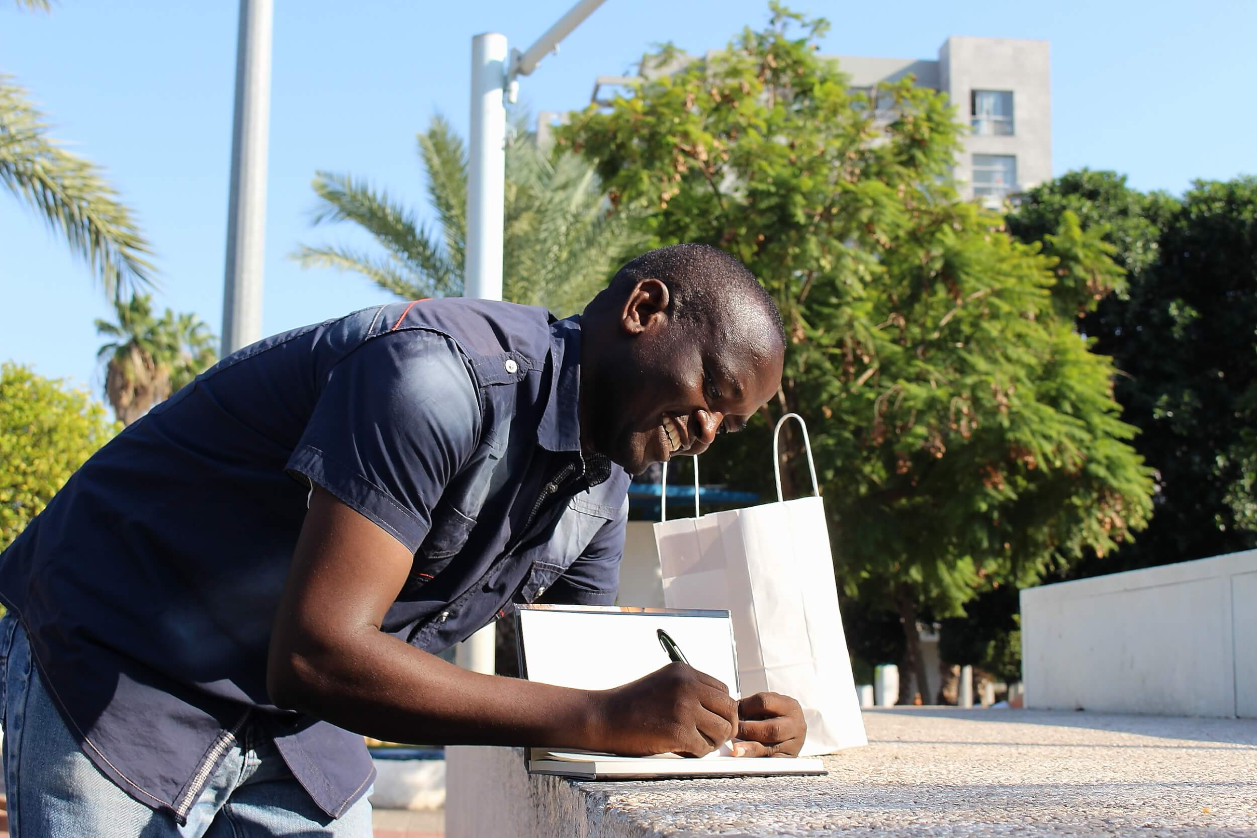 Adam Ahmad makes notes in his book, The Nightmare of the Exile, a book where he documents the racism he has experienced in Israel as a Sudanese refugee. (Photo: Matthew Vickery)