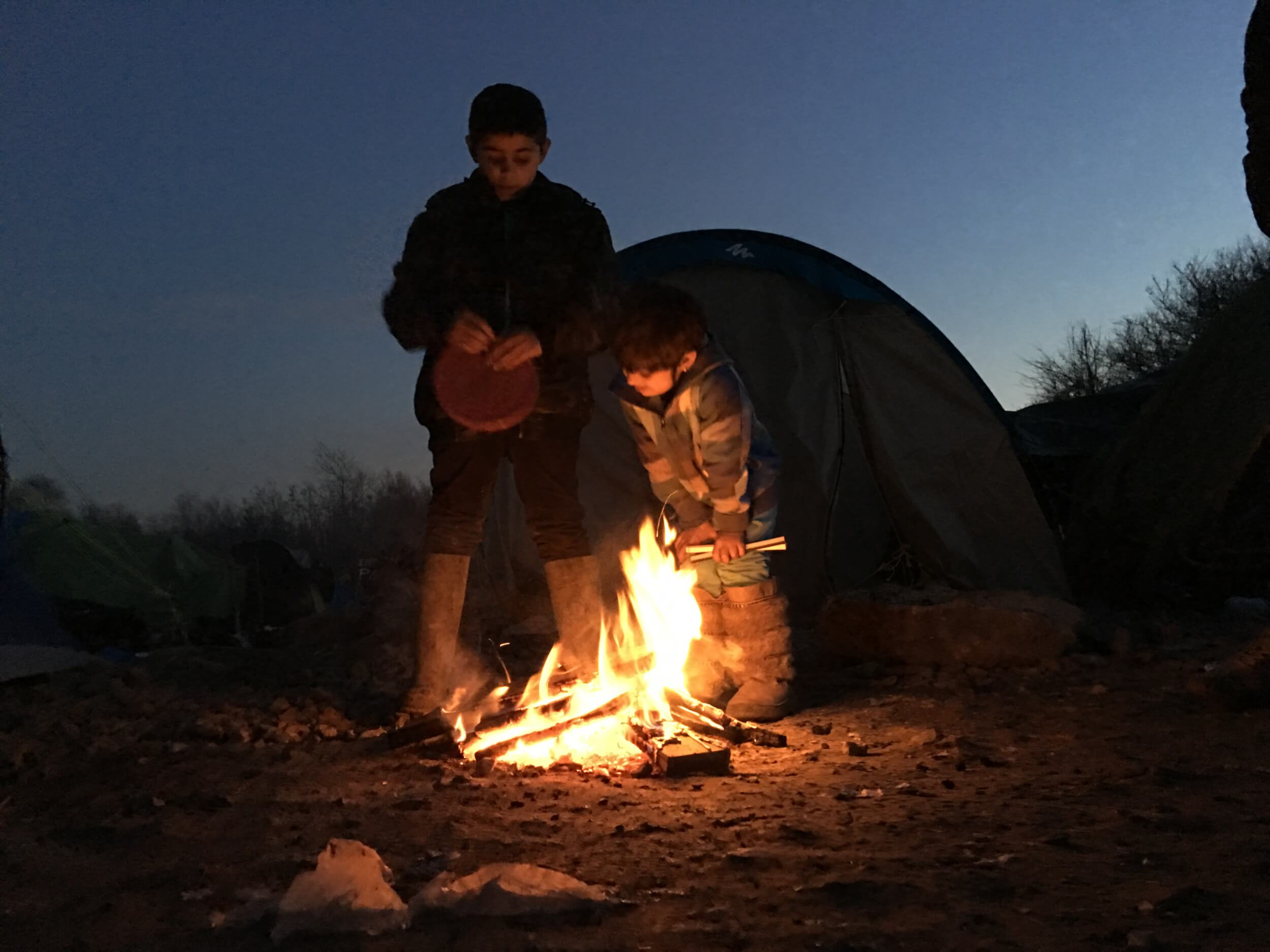 Anas, 10, and Shadi, 6 look on to a fire next to their tent. They have been in Grande-Synthe for eleven days. (Photo: Katherine Schwartz)