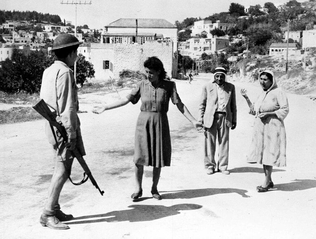 An Israeli soldier, armed with a rifle, stops Palestinians in a street in Nazareth, Palestine, July 17, 1948. (AP Photo)