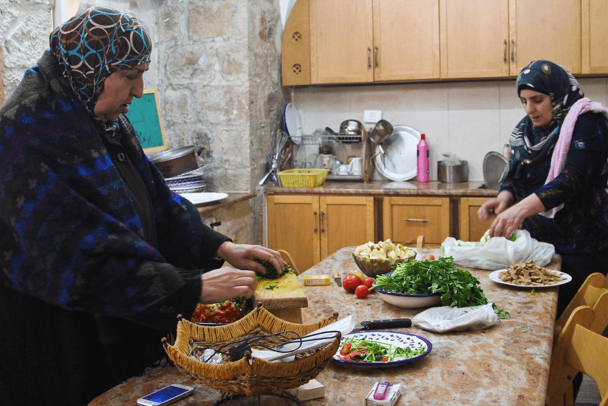 Women prepare ingredients in Beit al Karama kitchen. (Photo: Megan Hanna)