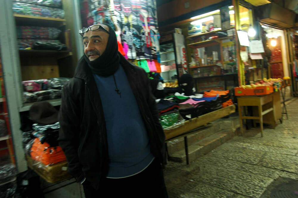 Alaa al-Din stands in front of his clothing stand in Jerusalem's Old City. (Photo: Allison Deger)