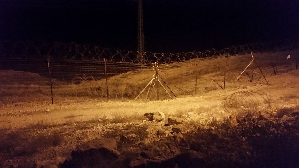 Walking the perimeter of kibbutz Naaran at night. Note the spools of concertina wire behind the similarly-topped fence