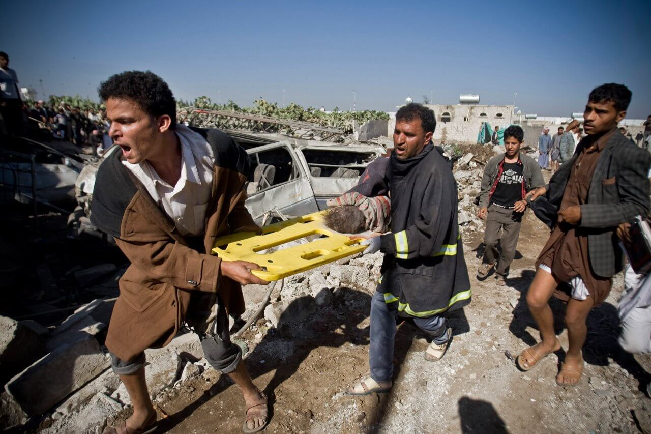 Yemeni civilians carry the body of a child they uncovered from under the rubble of houses destroyed by Saudi airstrikes near Sanaa Airport (Credit: AP/Hani Mohammed)