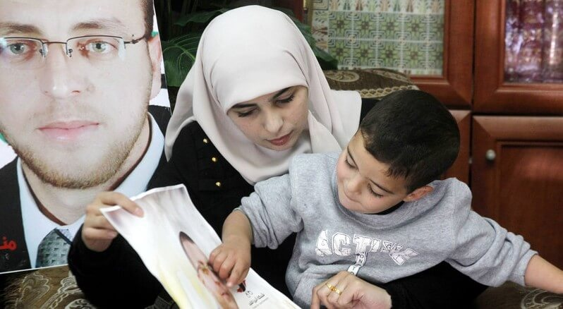 Fayha Shalash with her son and a photograph of her husband Mohammed al-Qiq, journalist and hunger striker in Israeli detention. Photo by Wisam Hashlamoun for APA Images