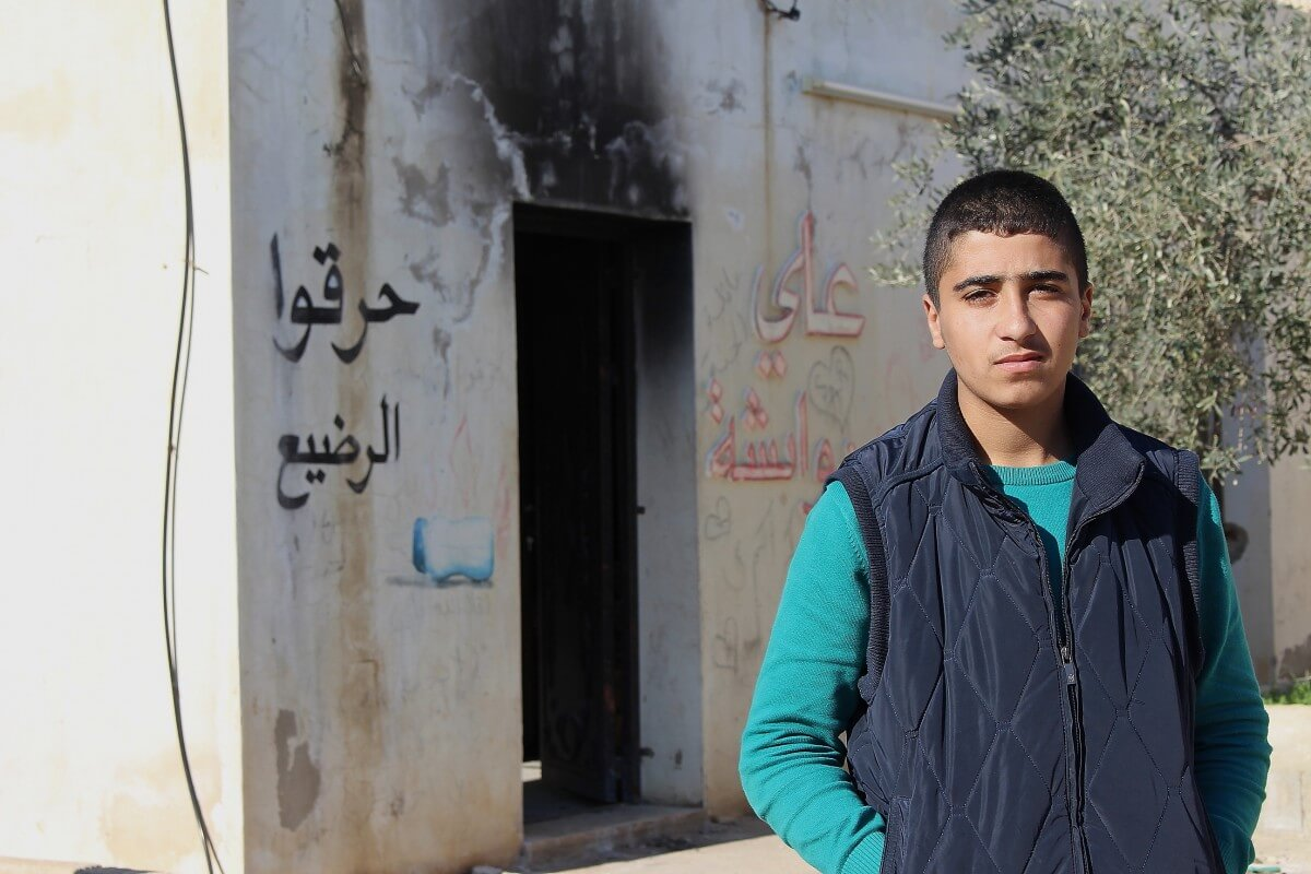 Baraa Dawabsha stands outside his relatives destroyed house. The residents of Duma say they don't feel protected and worry that a copycat arson attack could be round the corner. (Photo: Matthew Vickery)