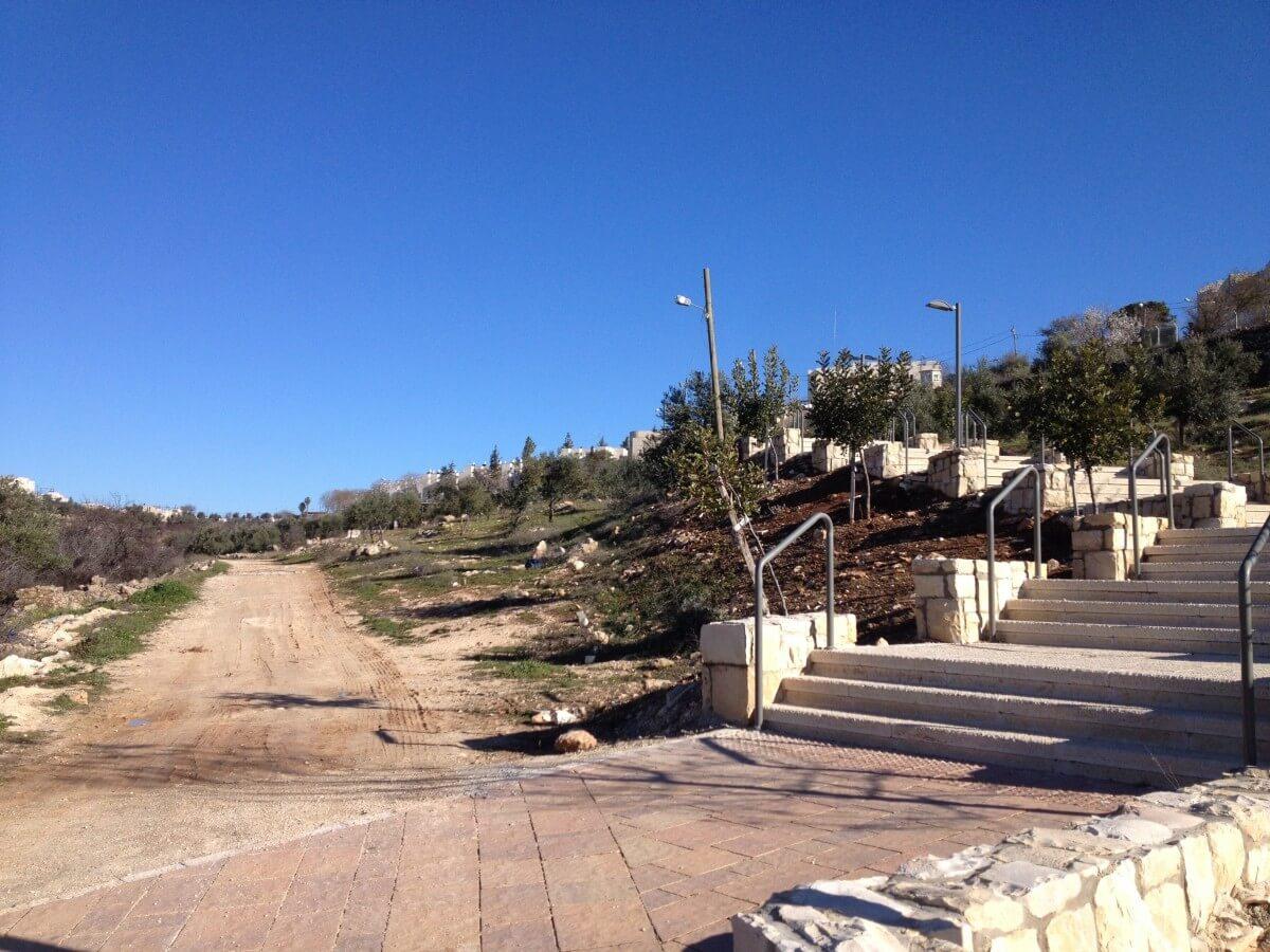 Asphalted pathway leading to Kiryat Arba next to an unpaved pathway leading to Palestinian houses in Wadi Al Hussein (Photo: EAPPI/Sabrina Tucci)