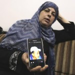 Suha Abu Khdier, mother of slain Palestinian teen Mohammed Abu Khdier, shows a photograph of her son who was abducted and burned alive in July 2014. (Photo: Reuters)