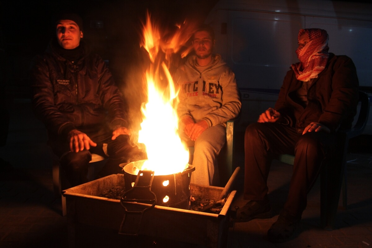 Palestinians warm themselves around a fire in Rafah in the southern Gaza Strip, January 14, 2014. The World Bank reported that 10% of Gaza's residents remain without electricity since the attack and the rest of the population has limited access to power. In December, Israel rejected a proposal to have a Turkish floating power-generating ship stationed off the coast to help solve the electricity crisis. (Photo:  Abed Rahim Khatib/ APA Images)