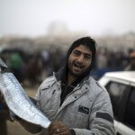 Samih al-Masri and a fish at the port in Gaza City, before logging onto Facebook.  (Photo: AFP PHOTO/MAHMUD HAMS)