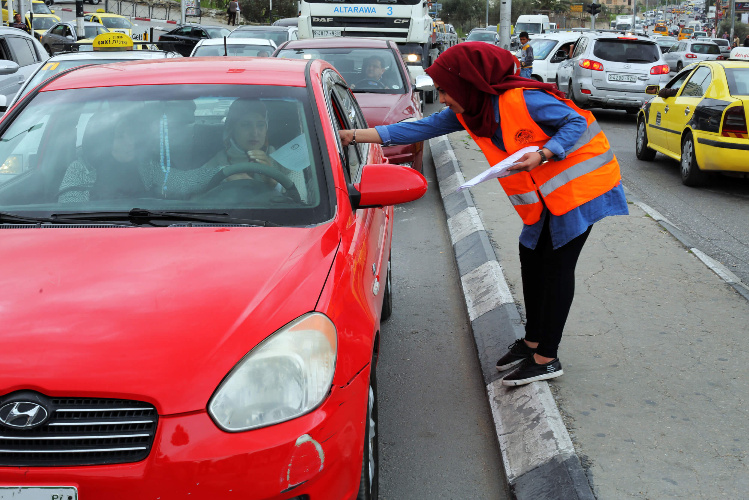 Student Rayda Izboon passes out flyers to local drivers explaining the importance of BDS. (Photo: Abed al Qaisi)