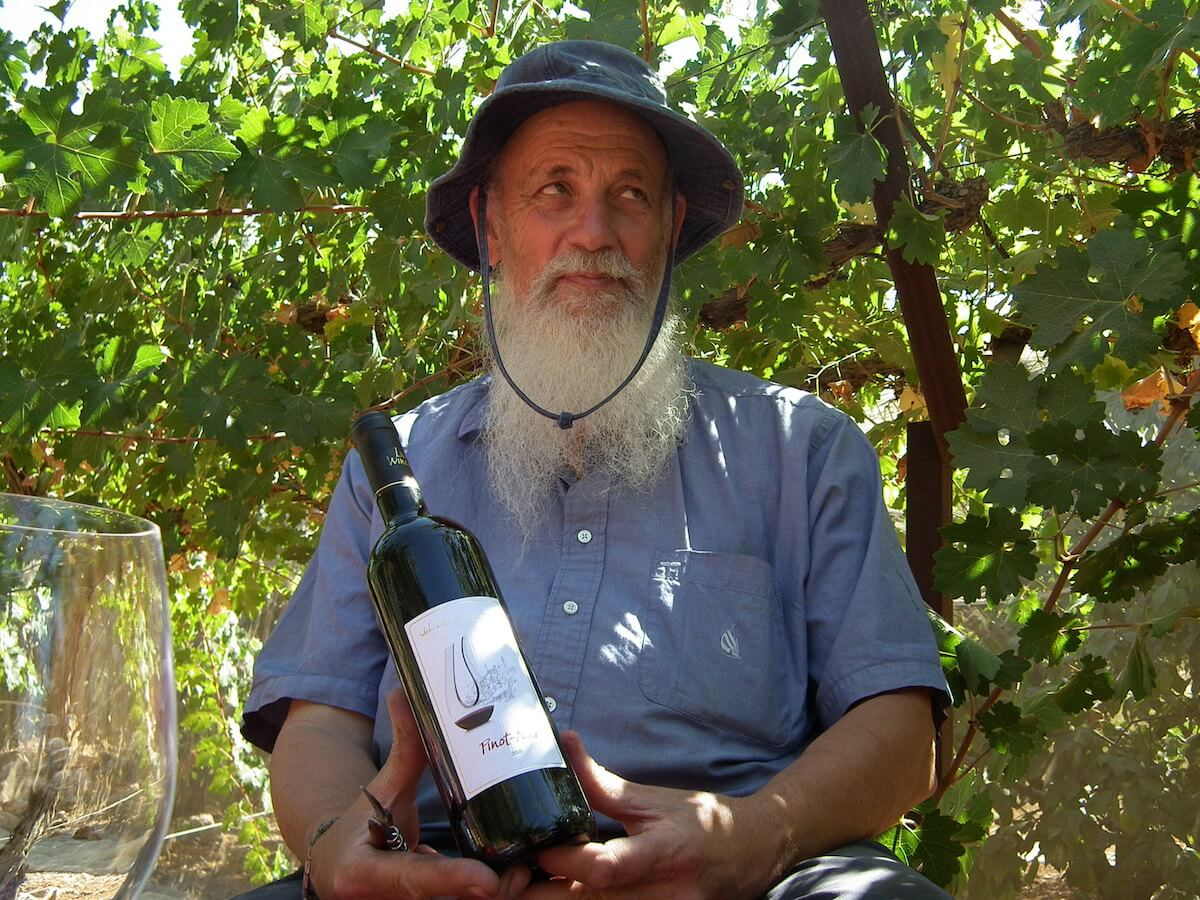 Menachem Livni poses with wine from his winery.