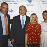 Left to right, is of Gidi Mark, CEO of Taglit-Birthright Israel; Israeli Prime Minister Benjamin Netanyahu looking at something; Netanyahu's wife, Sara Netanyahu looking at something else; and some other guy at a Birthright Israel Mega Event on June 24, 2014, in Caesarea, Israel.