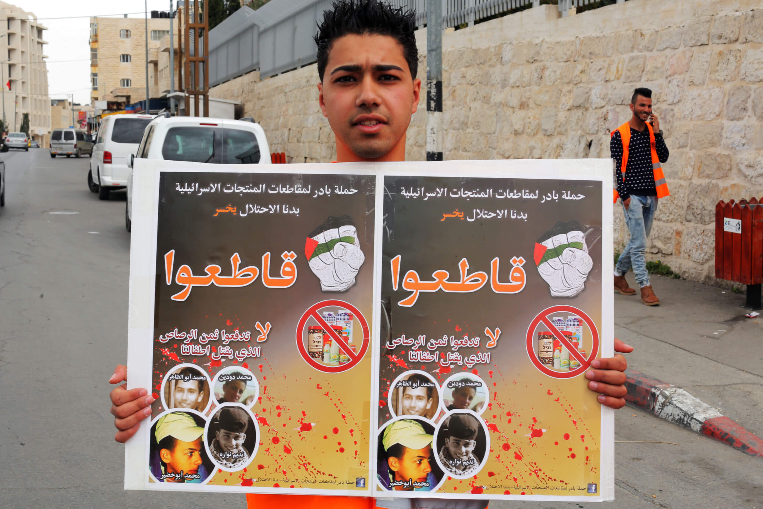 "Ibrahim Subhay holds a sign that reads ""Don't pay for the bullets that are killing our children."" (Photo: Abed al Qaisi)"
