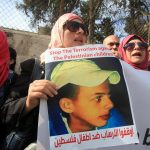 Protesters hold posters of Palestinian teenager Mohammed Abu Khdeir, who was killed last year, outside the district court in Jerusalem on November 30, 2015. The court on Monday convicted two Israeli youths in the grisly killing of Abu Khdeir, while delaying a verdict for 31-year-old Yosef Haim Ben-David in the case due to a last-minute insanity plea. The judge determined that Ben David, and two Israeli minors had snatched Abu Khdeir from an east Jerusalem sidewalk in July 2014 and burned him alive in a forest outside the city. (Photo: Mahfouz Abu Turk/APA Images)