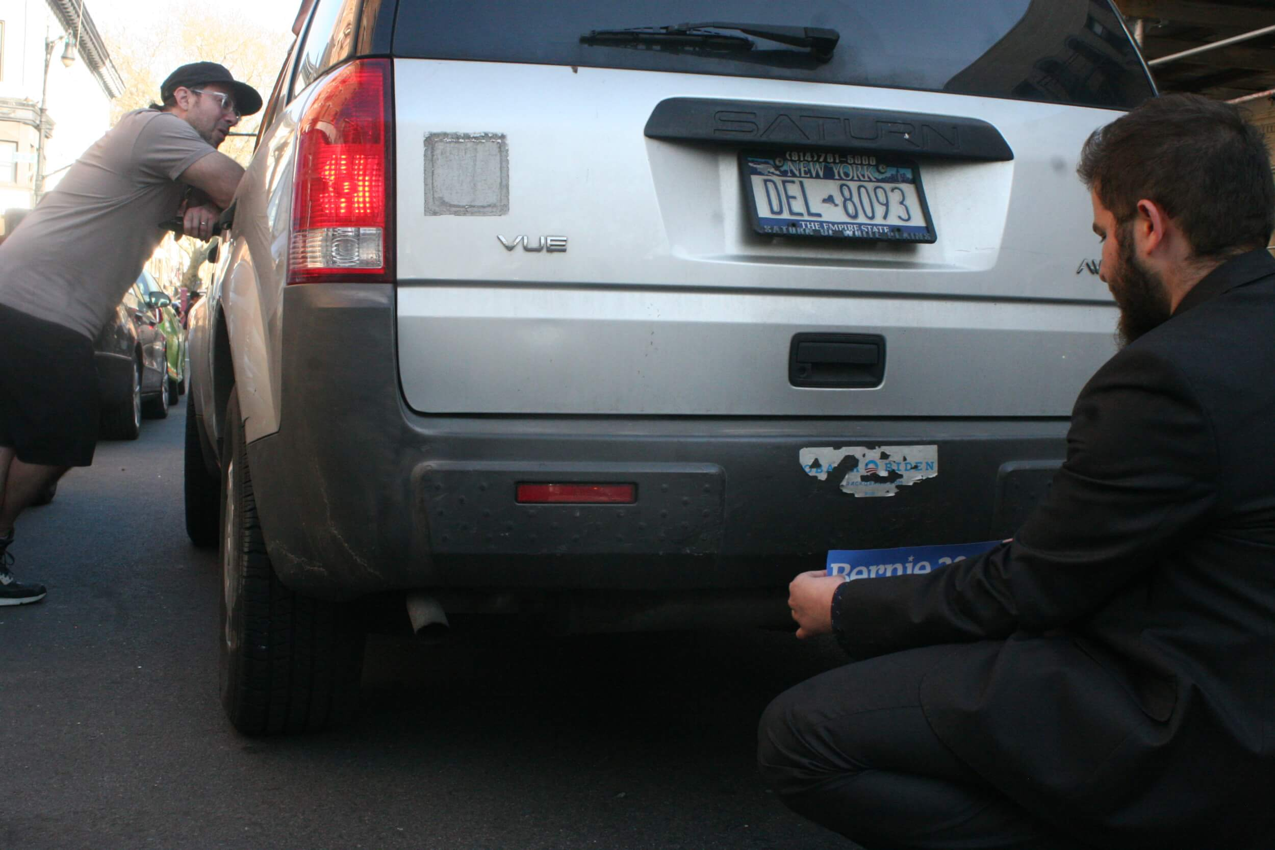 Abderahmanne Amor, an Algerian-American Sanders supporter and student at Ohio State, puts a Bernie Sanders bumper sticker over an ancient Obama-Biden sticker in Bay Ridge on April 19, 2016, the day of the New York primary, which Sanders would go on to lose.