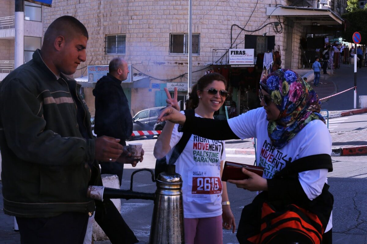 Some runners took the marathon with the upmost seriousness, while others had a bit of fun, like these women buying a cup of coffee in the middle of the race. (Photo: Sheren Khalel/Mondoweiss)