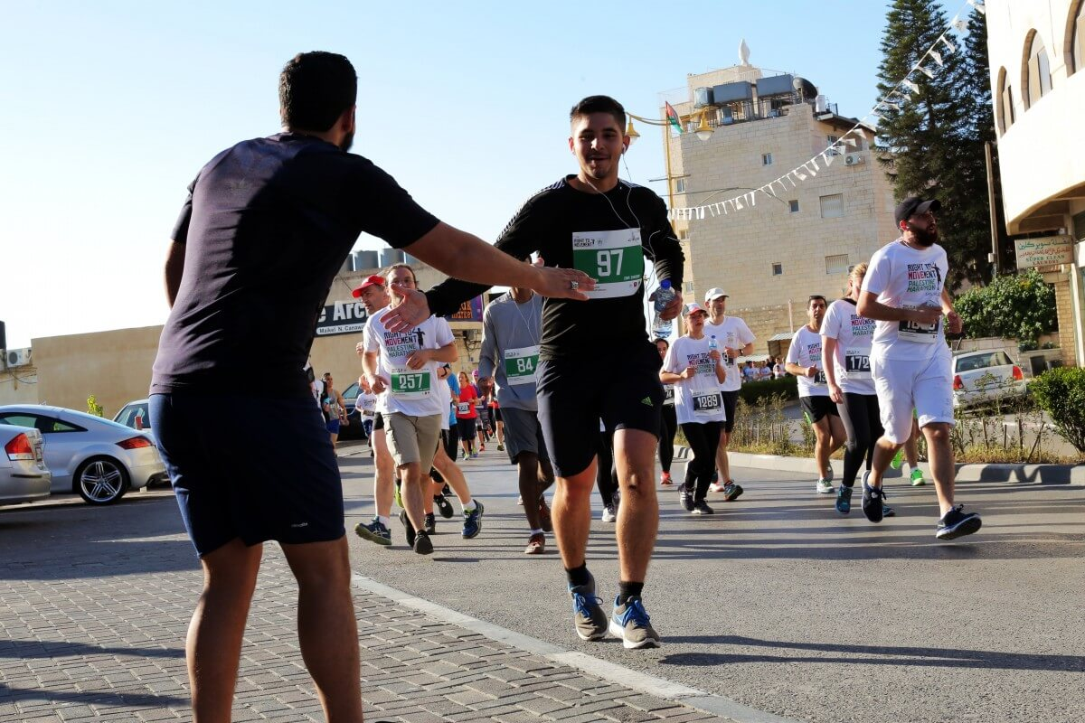 People were very supportive of each other, which hoards of people sticking around until the final runners came through, cheering runners on. (Photo: Sheren Khalel/Mondoweiss)