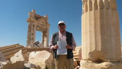 "Tour guide ""Tony"" in front of the ruins of the Temple of Baal blown up by Daesh' He's holding a drawing of the temple as it used to appear."