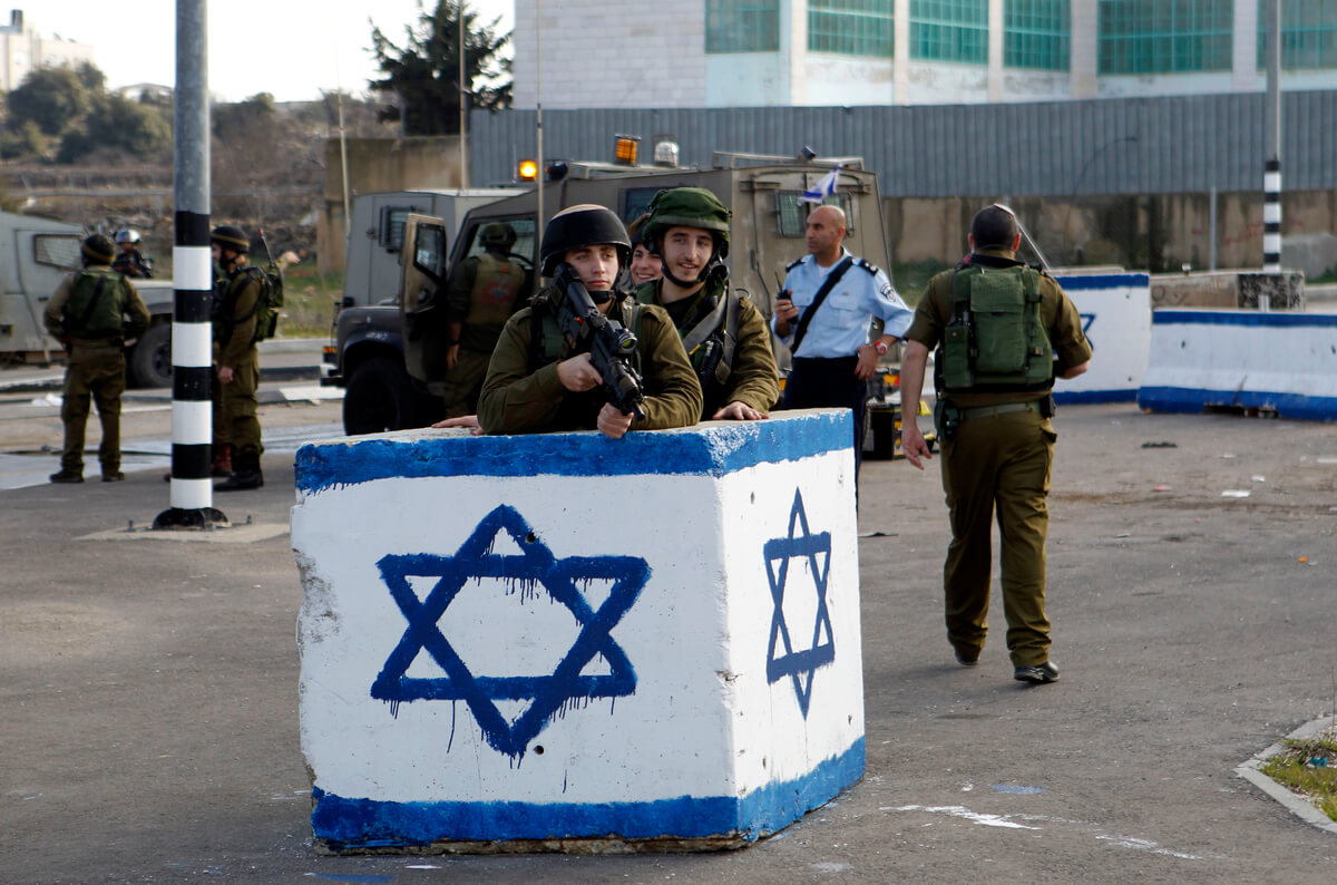 Israeli soldiers stand guard near the scene where two Palestinian men were shot dead by Israeli troops at the Beit Ainun junction northeast of Hebron in the occupied West Bank on Jan. 12, 2016. An Israeli army spokesperson said that Israeli forces shot and killed a Palestinian man after he allegedly attempted to stab soldiers at the junction. (Photo: APA Images/Wisam Hashlamoun)
