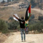 A Palestinian protester holds a Palestinian flag during clashes with Israeli troops at a protest ahead of Nakba day, in the West Bank village of Bilin near Ramallah May 13, 2016. (Photo: Shadi Hatem/ APA Images)