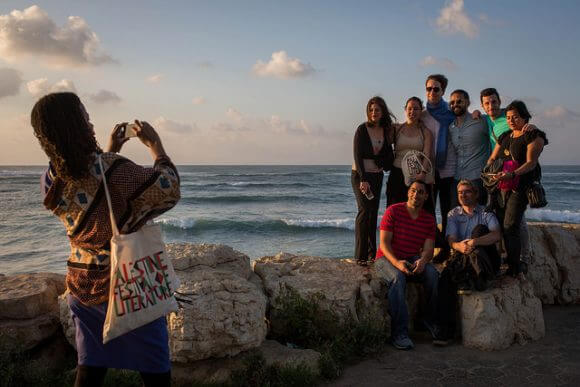 HAIFA, PALESTINE - MAY 24: Festival participants pose for a photograph at the Mediterranean coast on May 24, 2016 in Haifa, Palestine. (Rob Stothard for The Palestine Festival of Literature)